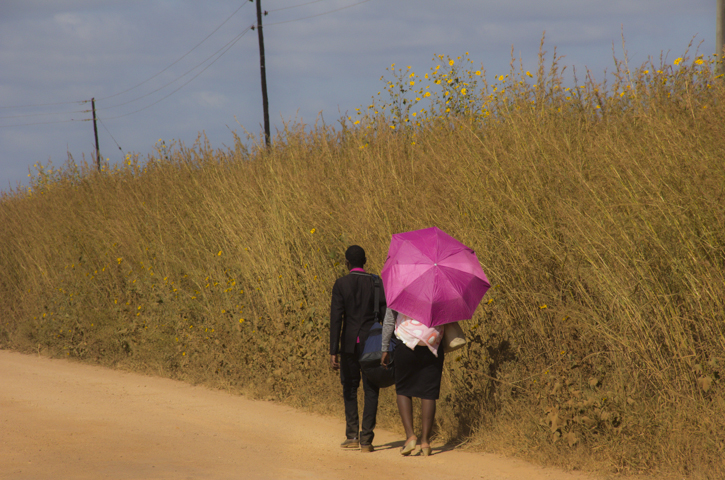 Walk in the dust. A couple walking near Shewula on the Lebombo Plateau in eastern Swaziland.